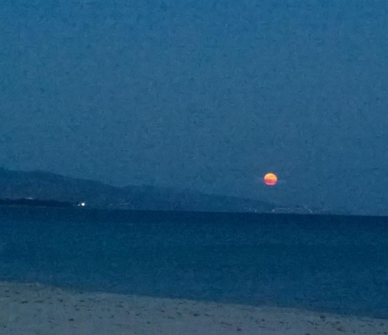 Luna ambrata di venerdì 13 giugno vista dalla spiaggia del Poetto